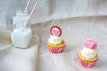 gum paste: Valentines french vanilla cupcake with heart gum paste topper. Valentines party treat with glasses of milk on natural burlap fabric background Stock Photo