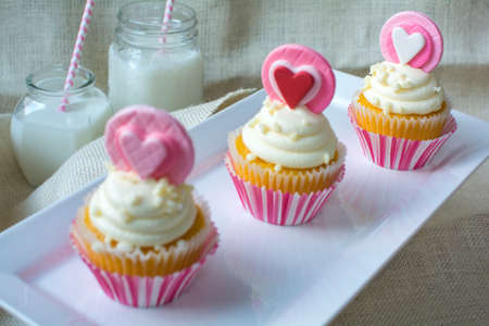gum paste: Valentines french vanilla cupcakes with heart gum paste topper in white square ceramic plate focus on the last cupcake. Valentines party treat with glasses of milk on natural burlap fabric background