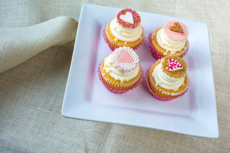 gum paste: Valentines french vanilla cupcakes with heart gum paste topper in white square ceramic plate. Valentines party treat on natural burlap fabric background
