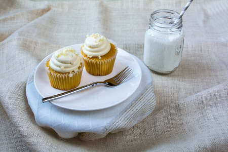 vanilla cupcake: French vanilla cupcake and a glass of milk in white ceramic plate on natural burlap color background. Vanilla cupcake and milk dessert. Stock Photo