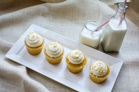 French vanilla cupcake and a glass of milk in white ceramic plate on natural burlap color background. Vanilla cupcake and milk bottles for dessert on white square ceramic plate