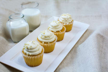 vanilla cupcake: French vanilla cupcake and a glass of milk in white ceramic plate on natural burlap color background. Vanilla cupcake and milk glasses for dessert on white square ceramic plate
