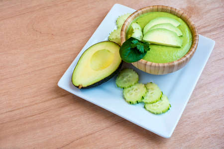 Chilled cucumber avocado soup in bamboo bowl on white square plate on wood background Stock Photo