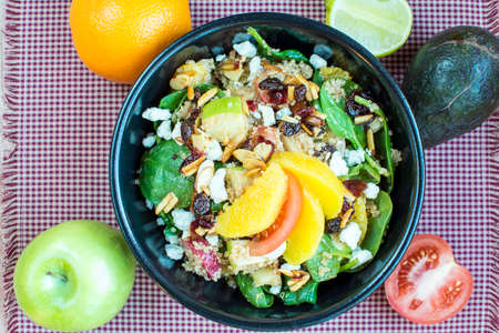 nutty: Spicy nutty fruity quinoa salad in black ceramic bowl., Homemade quinoa with spinach and fruit salad