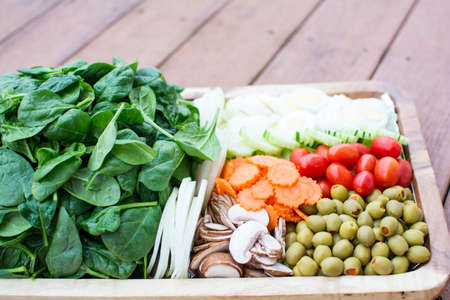 low carb diet: Fresh vegetable salad in wooden tray on strip background