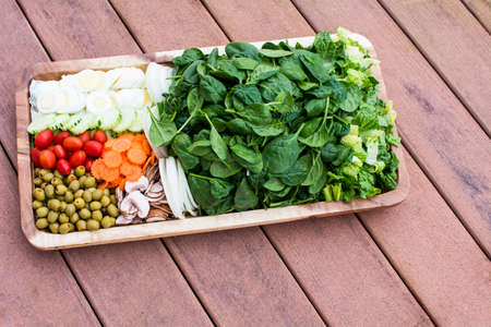 vegetable tray: Fresh vegetable salad in wooden tray on strip background