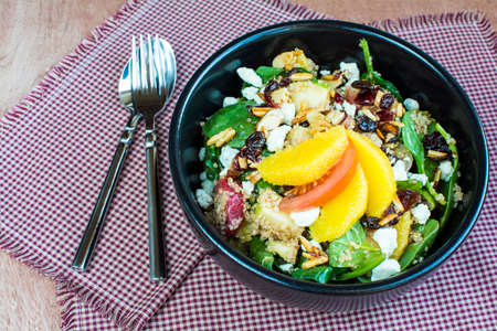 fruity salad: Spicy nutty fruity quinoa salad in black ceramic bowl., Homemade quinoa with spinach and fruit salad