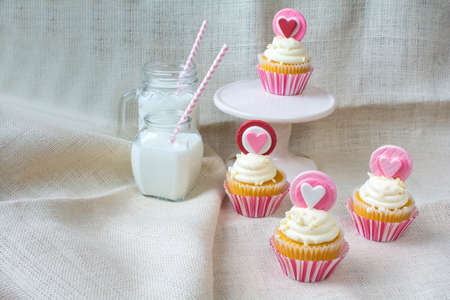 sweet treats: Vanilla cupcake with heart gum paste topper. Valentines party treat with glasses of milk on natural burlap fabric background