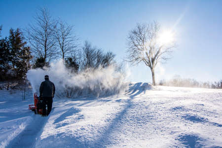 A man in black dress using a snow blower plowing snow after Jonas snow storm in the morning