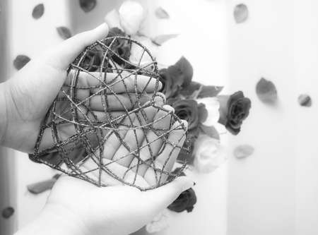 Hands holding glitter metal heart with some roses background in black and white Archivio Fotografico