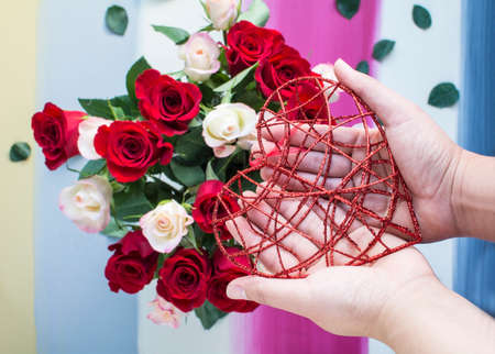 Hands holding glitter red metal heart with colorful painted and roses background Archivio Fotografico