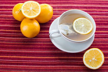 Lemon hot tea with tea bag in a cup and lemon fruits on red stripes platemat Archivio Fotografico