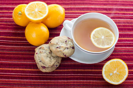 Lemon hot tea with white chocolate chip cranberry cookies and lemon fruits on red stripes platemat