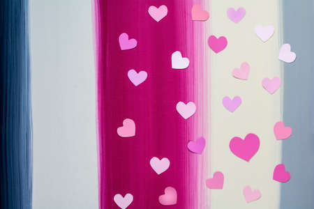 Valentine's paper heart patterns on colorful stripes painted wooden background