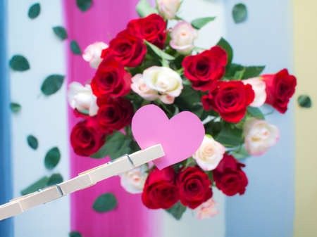 Valentine's paper heart with blurred roses on colorful stripes painted wooden background, Wood clothespins cliped on pink paper heart and roses background