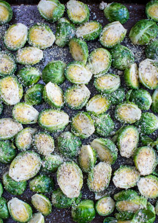 Fresh cut brussels sprout mixed with garlic parmesan cheese in baking sheet., Prepared fresh seasoning brussels sprout in baking sheet.