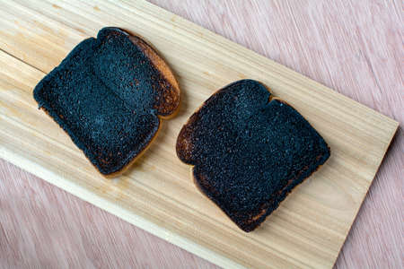 Two black burnt toast on wood flank with wood background Stock Photo