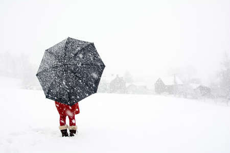 snow storm: A woman stand alone in snow storm watching  falling snow in the village, Red dress woman holding black umbrella standing in snow storm, Lonely woman in the winter wonderland