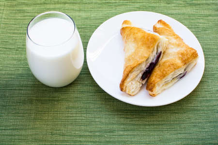 Glass of milk and two pieces blueberry cobbler puff pastries on white plate and green placemat background, Cobbler puff pastries breakfast and a cup of milk
