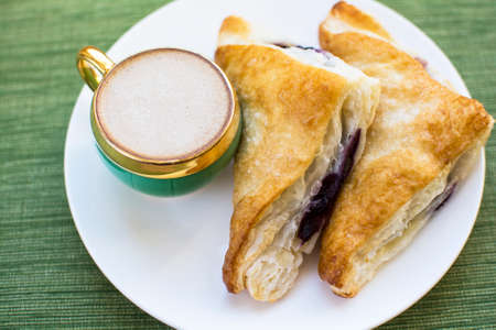 Mini cup of cappuccino and two pieces blueberry cobbler puff pastries on white plate and green placemat background, Cobbler puff pastries breakfast and a cup of coffee Archivio Fotografico