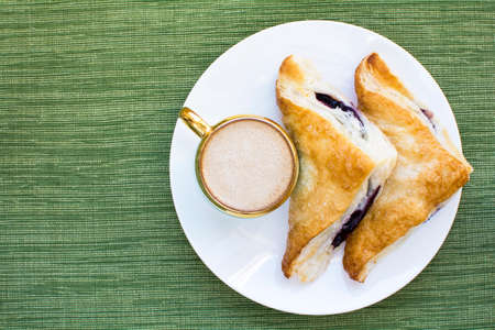 Mini cup of cappuccino and two pieces blueberry cobbler puff pastries on white plate and green placemat background, Cobbler puff pastries breakfast and a cup of coffee, Above shot cappuccino and blueberry cobbler breakfast