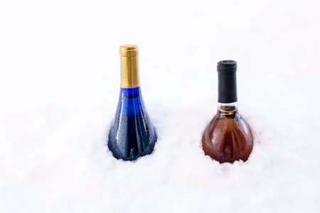 Two wine bottles chilling in white snow, Winter outdoor refrigerator, Cooking wine buried in the snow, Chilling wine bottles