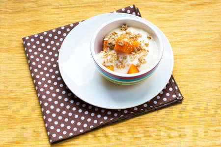 Healthy pumpkin yogurt dessert with maple granola topping, Healthy pumpkin snack bowl on yellow placemat Archivio Fotografico