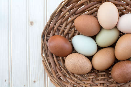 Colorful fresh organic chicken eggs in old dusty basket on wooden background, Colorful natural chicken eggs, Archivio Fotografico