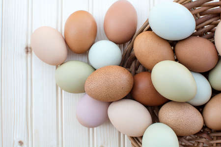 overflow: Colorful fresh organic chicken eggs overflow out of basket on wooden background, Colorful natural chicken eggs, Selected focus organic chicken eggs overflow out of the basket