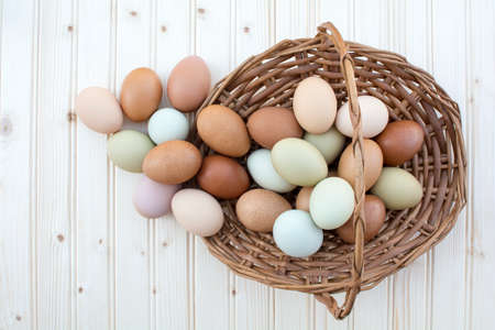 Colorful fresh organic chicken eggs overflow out of old dusty basket on wooden background, Colorful natural chicken eggs, Top view organic chicken eggs overflow out of the basket