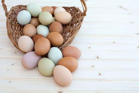 Colorful fresh organic chicken eggs overflow out of old dusty basket on wooden background, Colorful natural chicken eggs, Selected focus organic chicken eggs overflow out of the basket