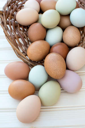 Colorful fresh organic chicken eggs overflow out of basket on wooden background, Colorful natural chicken eggs, Selected focus organic chicken eggs overflow out of the basket