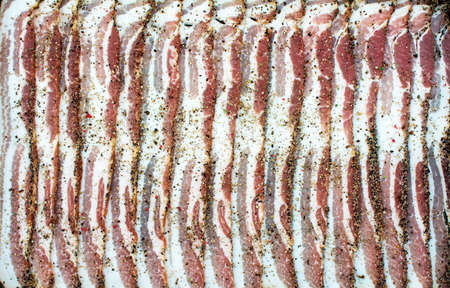 Pattern of raw sliced peppercorn bacon stripes