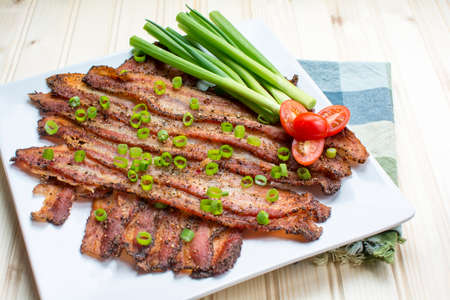 Oven baked peppercorn bacon garnish with chopped green onions with tomato and green onion on wood background