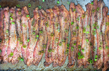 Oven baked peppercorn bacon garnish with chopped green onions in baking sheet