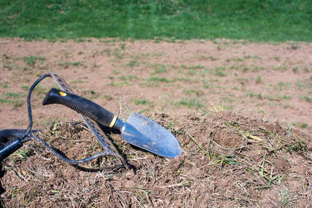dirt pile: Dirty gardening tools on pile of dirt and grasses
