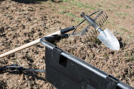 Dirty gardening tools on pile of dirt and grasses in black plastic yard cart, tools and dirts in wheelbarrow