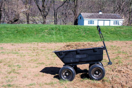 Black plastic yard card/ wheelbarrow full with dirt and grasses and old tool shed background Archivio Fotografico