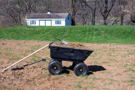 Pile of dirts and grasses in black plastic yard cart with gardening tools on top, tools and dirts in wheelbarrow with tool shed background