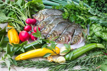 Cut and cleaned fresh perch fish on white cutting board with fresh organic vegetables on burlap background Stock fotó