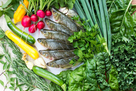 Cut and cleaned fresh perch fish on white cutting board with fresh organic vegetables on burlap background Archivio Fotografico