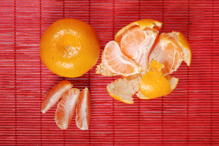sours: juicy yellow and tangerines on red background Stock Photo