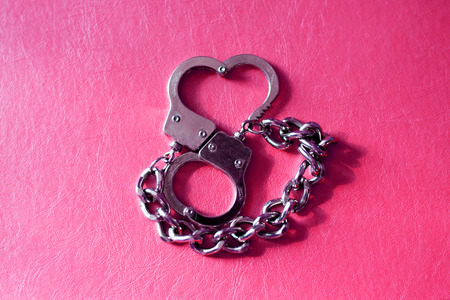 metal handcuffs: metal handcuffs in shape of heart at red background Stock Photo