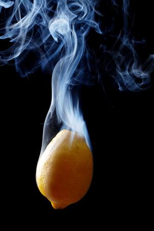 enveloped: yellow lemon enveloped by smoke on a black background Stock Photo