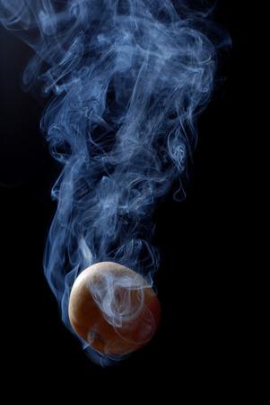 enveloped: yellow apple enveloped by smoke on a black background