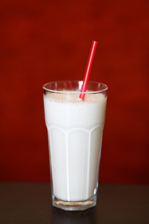 red straw: Glass of milk shake with red straw on red background Stock Photo