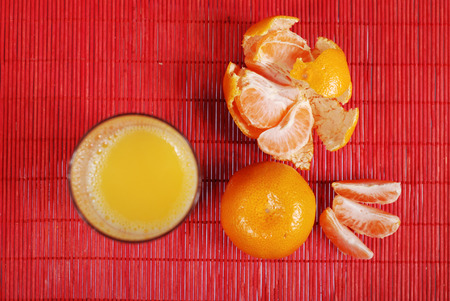 sours: glass of orange juice and tangerine on red background Stock Photo