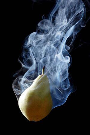 enveloped: green pear enveloped by smoke on a black background Stock Photo