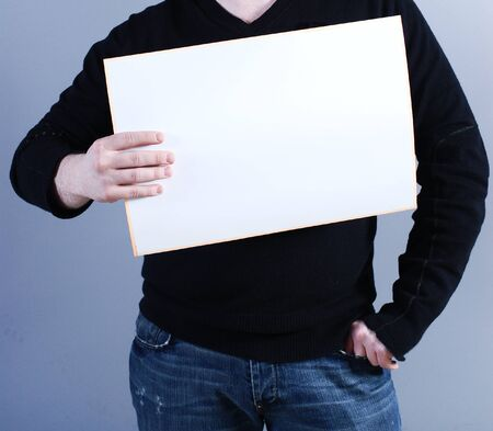 a placard: Man takes placard at blue background Stock Photo