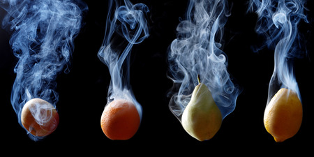 enveloped: set of fruits enveloped by smoke on a black background